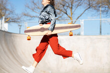 Excited Woman With Longboard Jumping Against Leafless Trees In Town