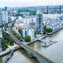 River Thames , London. River Front Buildings And Battersea Railway Bridge