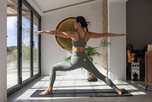 Flexible Woman Performing Warrior Two Pose Indoors