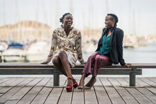 Cheerful Black Girl Friends Laughing Sitting On Bench