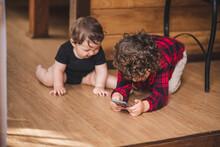 Cute Siblings Sitting On Wooden Floor In House