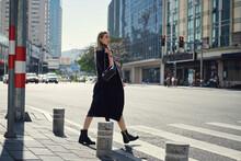 Stylish Woman Crossing Urban Road