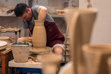 Focused Man Sculpting With Clay In Workshop