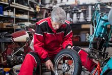 Senior Mechanic Fixing Wheel Of Motorcycle In Workshop