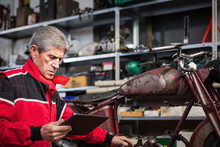 Senior Mechanic With Tablet Repairing Motorcycle In Garage