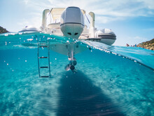 Half Underwater Of A Rubber Dinghy With A Outboard On A Turquoise Clear Sea.