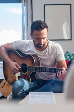 Bearded Ethnic Man Reading Notes And Playing Acoustic Guitar At Home