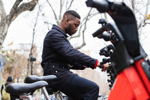 Attentive Ethnic Man Using Smartphone App On Bicycle Parking