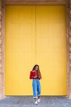 Black Woman Standing Listening To Music Near Huge Doors In City