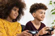 Cheerful Ethnic Kids Playing Video Game With Joysticks