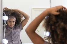 Crop Ethnic Girl Touching Hair Against Mirror In House