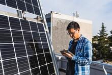 Focused Ethnic Engineer Using Tablet Near Solar Panel