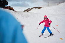 Unrecognizable Parent And Kid Skiing On Snowy Hill Slope