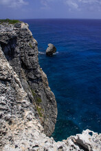 A Shot Taken From The Top Of The Bluff In Cayman Brac. The Limestone Cliff Face Drops Down Into The Crystal Clear Blue Water With A Rock Formation Called Little Cayman Brac Breaching The Surface