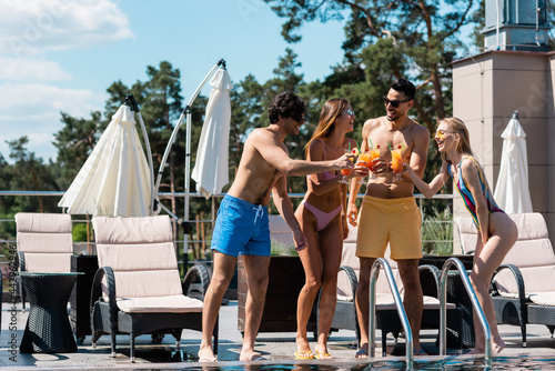 Fotografie, Obraz Multiethnic people in swimwear toasting with cocktails near swimming pool