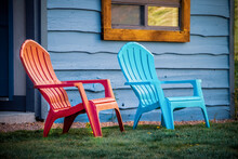 Close-up Of Red And Turquoise Arondiack Chairs Sitting Outside Blue Wooden Cabin Door On Grass.