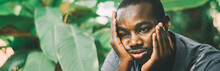 Unhappy African Man Having Puzzled Expression, Holding Hand On His Cheek. Black Male Feeling Bored Or Depressed