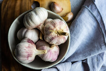 Bowl Of Fresh Cloves Of Garlic And Garlic Bulbs On A Table