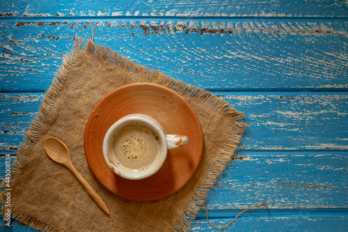 Fototapeta Cup of hot coffee in the morning on a blue rural wooden table