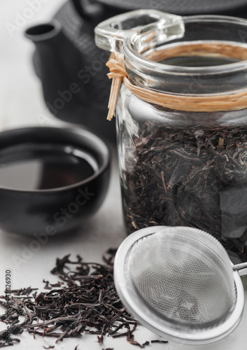Fototapeta Glass jar of black loose organic tea with teapot and cup with tea strainer infuser on white background