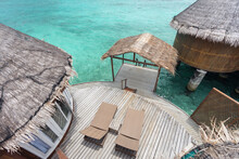 Water Villas With Deckchairs On Sunny Day