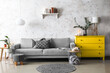 Trendy interior of living room with grey sofa and yellow commode