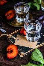 Two Glasses Of Plum Vodka On A Table With Fresh Plums