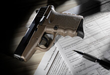FBI NICS Check Form That Is Public Domain With A Brown Polymer Handgun And Pen