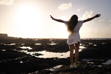 A Blonde Woman With Curly Hair And A White Dress Standing With Her Arms Wide Open Looking Out To Sea With A Sky Full Of Clouds And Colors At Sunset. Concept Of Peace, Relaxation, Tranquility, Happine