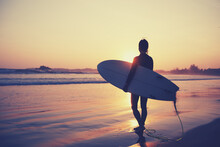 Woman Surfer With Surfboard On Sunset Beach