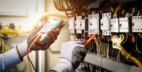 Fotografie, Obraz Electrical engineer using digital multi-meter measuring equipment to checking electric current voltage at circuit breaker and cable wiring system in main power distribution board
