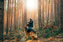 Man Walking With Shepherd Dog In Forest