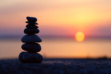 The Stones Of The Pyramid Balance On The Rock At Sunset. The Background Of The Evening Sea Is Blurred. Selective Focus.