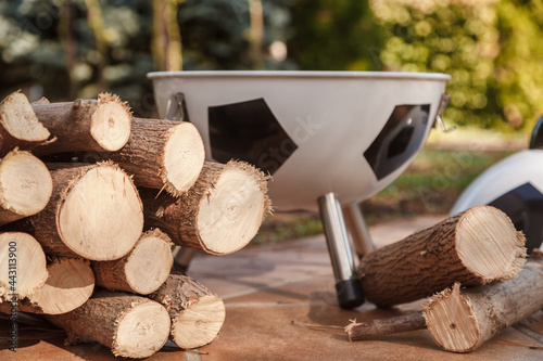 Fototapeta Bunch of round firewood lies in yard. Round brazier back