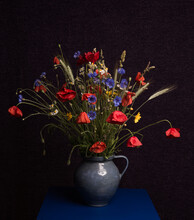 Bouquet Of Wild Flowers In A Blue Vase In Classic Dark Painterly Studio Setting