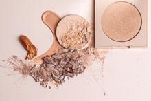 Crushed Beige Face Finishing And Liquid Powder, Smashed Lipstick And Cracked Eyeshadow. Macro Texture Of Make-up On Beige Background