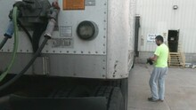Young Truck Driver Approaching The Side Of A Trailer And Starting To Lower Landing Gear In Order To Uncouple The Truck. He's Parked On A Dock Of A Warehouse. A Green Light Is Flashing Behind Him.