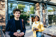 Young Handsome Caucasian Curly Man Waiting For His Girlfriend In The City Street, Outdoor. Love, Relationship, Dating: Concept. French Curly Male Student And African Millennial Female On Background.