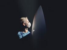 Man Posing Near Surfboard In Darkness