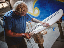 Man With Scissors And Tapes Decorating Surf Board