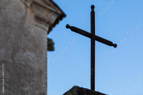 Sagoma di crocifisso su cielo azzurro di fronte ad una chiesa. Fototapet