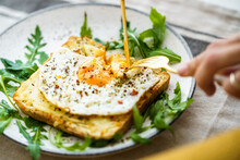 Anonymous Person Eating Toast With Eggs And Cheese