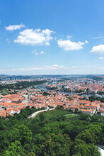 Panorama Of City With A Wide River In Summer. River In A European City With Red Tile Roofs. View Of The Cozy Streets Of The Old Czech City On A Background Of Blue Sky.