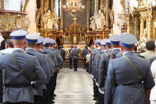 Polska policja w galowych mundurach na uroczystości w kościele.