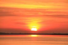 市街地から昇る太陽と真っ赤な朝焼け