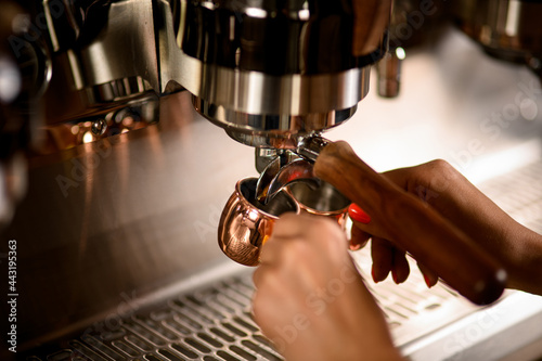 Close-up view of freshly brewed espresso pouring from the coffee machine into cu Fotobehang