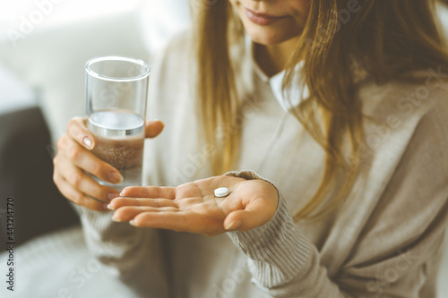 Cuadros en Lienzo Close-up woman holding pills time to take medications, cure for headache, high blood pressure or cholesterol level remedy pain killer drugs