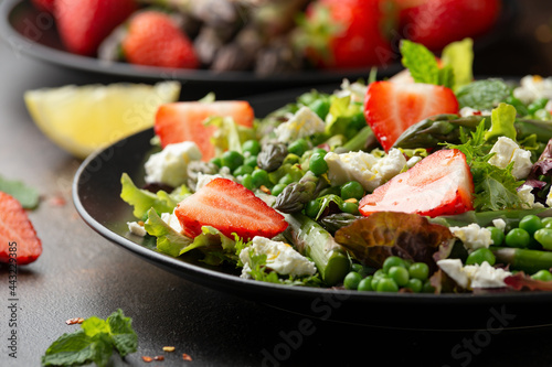 Asparagus and Strawberry Salad with vegetables, green peas and feta cheese in black plate Fototapet