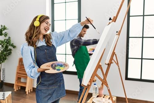 Two hispanic students smiling happy painting at art school Fototapet
