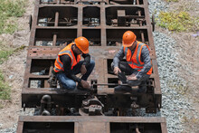 Worker On A Site. Top View Two Service Engineer On The Bogie And Checking Joint.